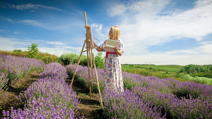 Beautiful young woman in long dress painting picture of lavender field at Provence