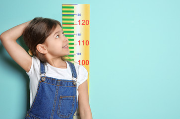 Little girl measuring her height on color background