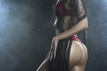 Torso of slim girl wearing a red lingerie and black veil posing from her back in rain water drops in a studio shows her beautiful butt on black in a theatrical smoke