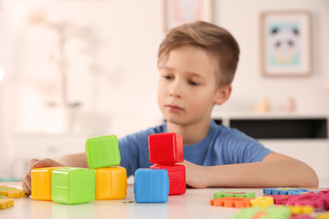 Little boy with autistic disorder playing at home, closeup of cubes