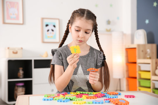 Little autistic girl playing with puzzles at home