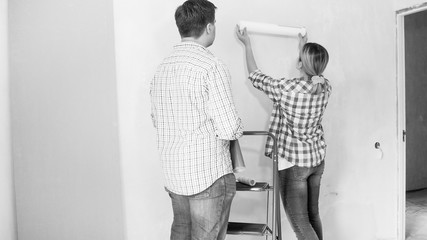Black and white image of young couple choosing wallpapers in new home