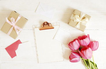 Feminine desktop composition with blank greeting card sheet clipboard, envelope, pink tulips bouquet, craft paper present wrap on white wood table background. Top view, flat lay, close up, copy space.