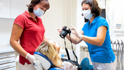 Portrait of dentist using digital camera to make image of patients teeth