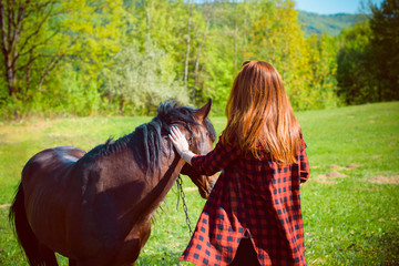Young woman taking care and talking to a horse on a hot autumn day at village. Beautiful young female walking and hugging with her brown horse outdoor