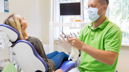 Portrait of male dentist sitting in office and wearing latex gloves
