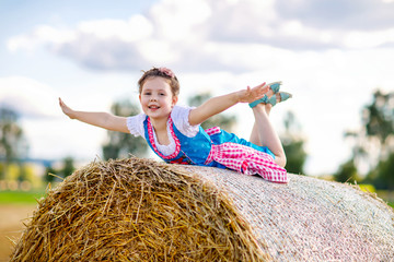 Cute little kid girl in traditional Bavarian costume in wheat field