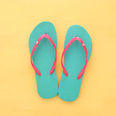 vacation and summer image with flipflops over yellow wooden background.
