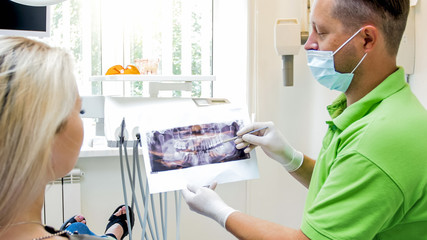 Portrait of dentist showing x-ray image to his female patient