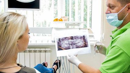 Portrait of satisfied dentist showing x-ray image of perfect teeth to his patient