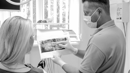 Black and white image of dentist showing x-ray image to his woman patient
