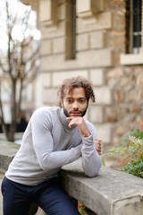 Black boy wearing grey turtleneck sweater standing near concrete banister near brick wall background. Concept of international student and businessman.