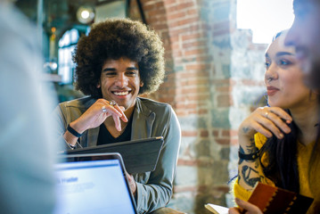 Afro american man with tablet smiling at colleagues or clients.Group of multiethnic people having business team meeting in restaurant lounge.Teamwork,corporate,diversity and social concepts.