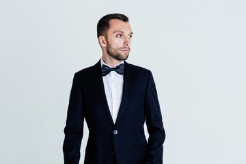 Stylish young man in black suit and bow tie