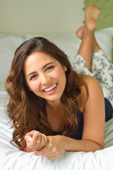 Young hispanic woman lying in a bed.