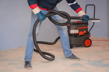 cleaner in special clothes and rubber gloves holds a knot of corrugated hose from an industrial vacuum cleaner. Cleaning services rooms
