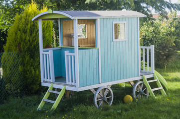 blue wooden children's playhouse on wheels in the yard