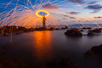 A ring of fire spinning steel wool on the rock and beach, Showers of hot glowing sparks from spinning steel wool on the rock and beach.