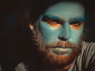 Portrait of a man with a blue make-up on his face. Stage make-up, like an alien, fantasy.