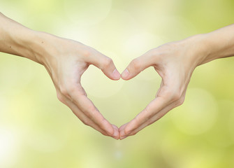 close up man hands making heart on blurred bokeh nature backgrounds for lover fall in love concept.