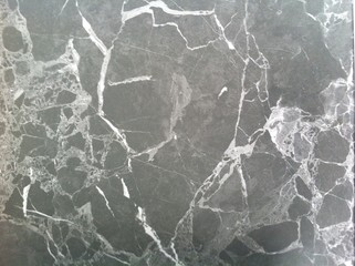 Dark marble texture. Polished natural stone with white veins, lines.
