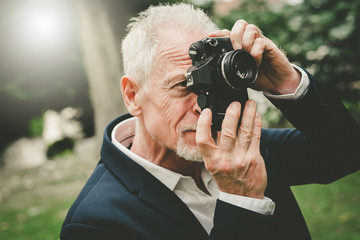Mature man taking pictures, light effect