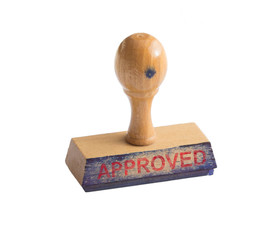 Used, ink stained stamp on a white background with the word Approved