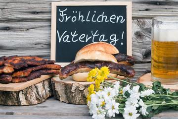 """Tafel mit Text """"Fröhlichen Vatertag"""" mit Bier-Bratwurst und Bauchfleisch rustikal vor Holzhintergrund"""