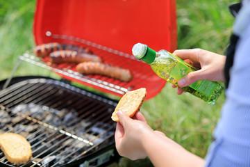 Kobieta polewa olejem pieczywo przed pieczeniem na grilu turystycznym.