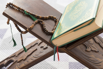 Koran , the holy book of moslems on the lectern with rosary . ramadan concept