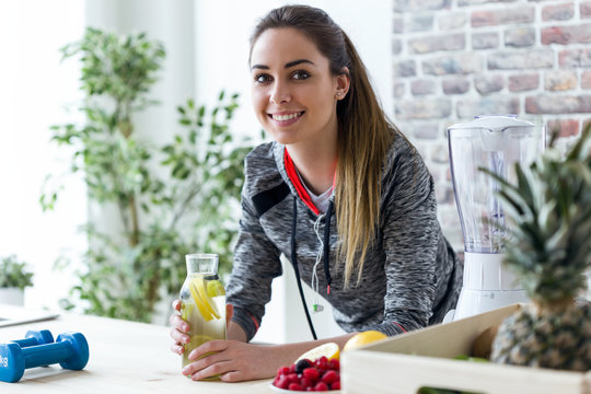 Sporty young woman looking at camera while drinking lemon juice in the kitchen at home.