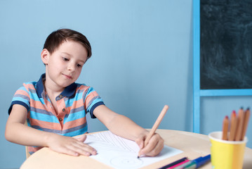 Cheerful Caucasian boy spending time drawing with colorful pencils at home.