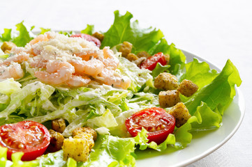 shrimps, lettuce, tomatoes,and croutons salad sprinkled with grated cheese