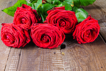 Red rose flowers on old wooden  background, horizontal.
