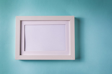 Mockup. Minimalism style. White empty picture frame against; blue color paper background; flat lay; copy space.