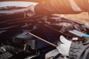 Close-up of auto mechanic diagnoses car using tablet computer.