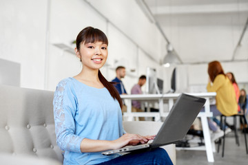 business, education, technology and people concept - happy young asian woman with laptop computer working at office