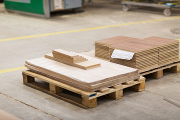 production, manufacture and woodworking industry concept - wooden boards and chipboards storing at furniture factory