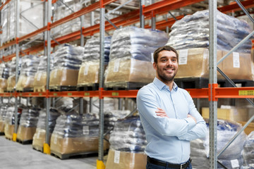 logistic business, shipment and people concept - happy businessman at warehouse
