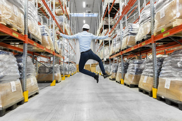 Obraz logistic business, success and people concept - happy businessman in helmet jumping at warehouse - fototapety do salonu