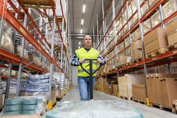 logistic business, loading and shipment concept - warehouse worker carrying loader with goods