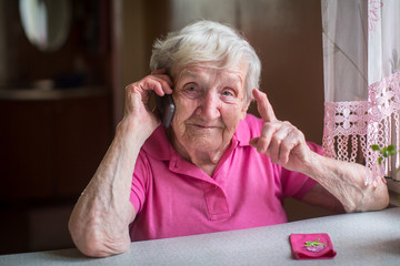 An elderly woman talking on a mobile phone sitting at a table in his house.
