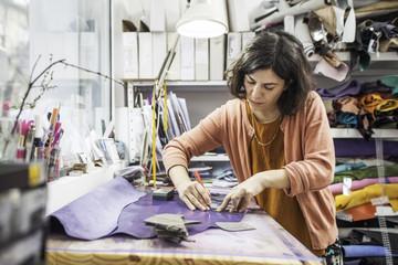 Woman designer making handmade shoes in her workshop