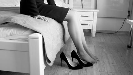 Black and white closeup image of young woman sitting on bed and taking off high heels shoes