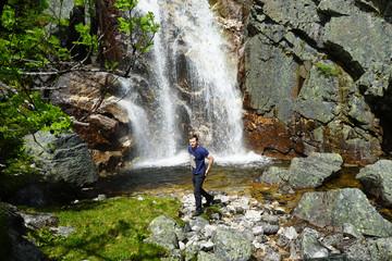 A man standing near waterfall.