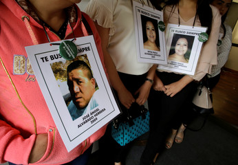 Relatives hang portraits of family who went missing in 2009, allegedly as a result of human rights violations by the Mexico military in San Jose
