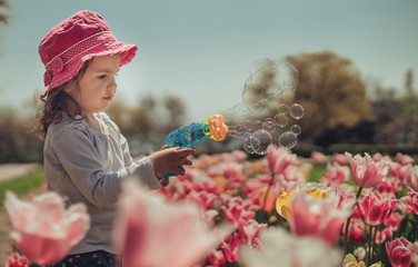 Little girl blowing soap bubbles in summer park with blooming flowers and tulips