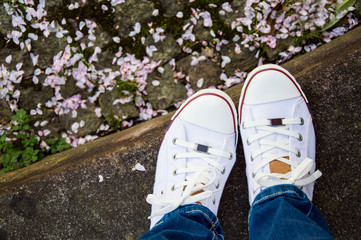 feet shod in white shoes on a spring day petals of flowers lying on the ground.jeans and moccasins
