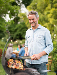 in the summer, watching the camera a handsome man in his forties prepares a barbecue for his friends gathered around a table in the garden