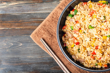 Fried rice with vegetables and pork in a pan, Asian cuisine, top view of food